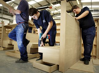 Apprentice joiners working in a factory