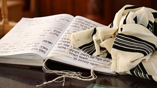 A  prayer shawl, known as a tallith, which is a Jewish religious symbol, with a Jewish prayer