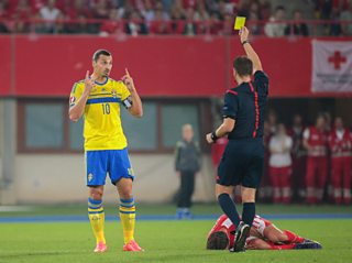 Referee giving a yellow card to footballer