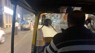 A man driving a tuk tuk.