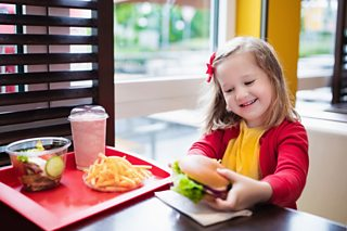 A child eating in a fast food restaurant.
