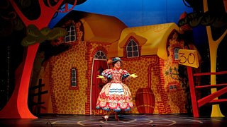 A dame is on stage in a pantomime performance - they are wearing elaborate and colourful costume and stand amongst a bright village set.