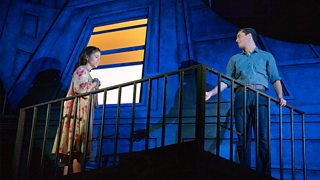 Two performers are on stage within dark blue lighting to represent the night time - the window behind them is illuminated orange.