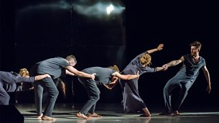 Five performers are in a line on stage in a physical theatre performance - four grasp each others waists and the fifth pulls them forward by the hand.