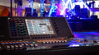 A sound control panel sits in front of an array of coloured lights, featuring a large screen, several channel sliders and a variety of buttons and dials.