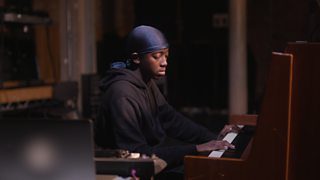 Sound designer Duramaney Kamara plays the piano while creating a score for a theatre performance.