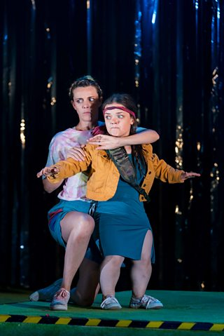 One actress holds another actress on stage in Pity