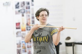An actress rehearses with a wooden pole prop