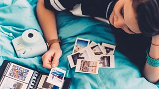 A teen girl looking at polaroid pictures.