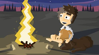 A prehistoric era child sits with his dog by a fire, dressed in animal furs to keep warm
