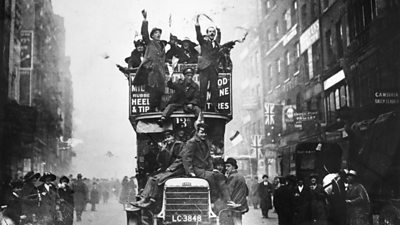 People celebrate the end of World War One on a London bus