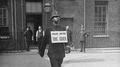 Policemen warning people to take cover during an air raid in World War One