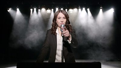 With dramatic lights behind her, a woman gives a speech whilst pointing at the viewer.