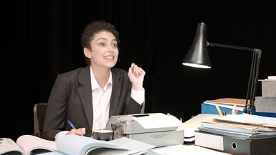 A woman in a business suit sits at a desk surrounded by papers and a typewriter.