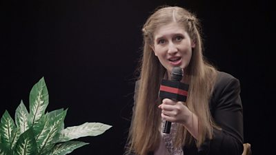 Presenter holds a microphone with a plant next to her