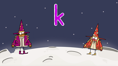 On the moon, two happy wizards, one purple, one red, stand next to the letter 'k'