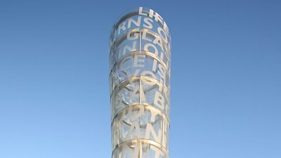A round tubular sculpture with words encompassing it, seen against the sky.