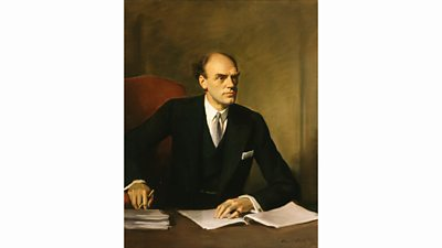 Portrait of John Reith seen at his desk signing papers. He looks characteristically serious.