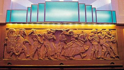A frieze consisting of figures dancing in a procession in costumes and fancy dress. Above is an art deco light.