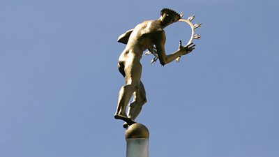 A bronze statue of a muscular nude man holding a ring of fire representing the Sun. He stands atop the world.