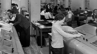 A busy scene of men and women operating various large pieces of equipment while journalists sit at desks in the background.