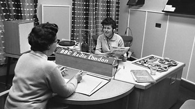 Two women sitting page-to-face discuss the newspapers in a studio. A reel-to-reel deck and a record deck can be seen.