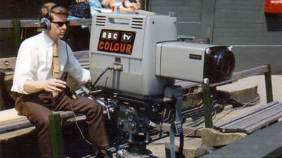 A cameraman in shirt and tie operates a large grey camera.