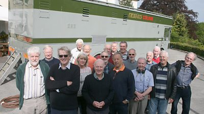 Veteran Crew Group Shot. 19 people stand in front of a large rectangular scanner van with BBC tv colour on the side.