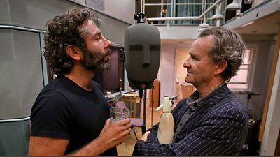Two actors stand at both sides of a binaural head microphone.