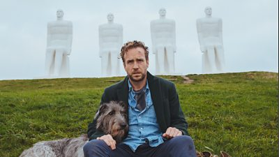 Rafe Spall looks dishevelled sitting next to a Danish statue, his arm around an equally sad looking Irish Wolfhound