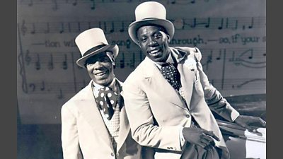 Two black singers in white coats, spotted cravats and top hats.