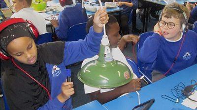 Three children wearing headphones tap a green lampshade.