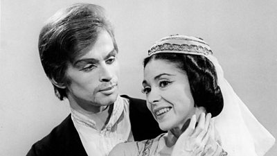 A man and a woman, heavily made up, the woman in a headdress. Margot Fonteyn is on the right.