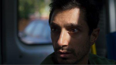 Riz Ahmed in a van looking tense.