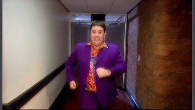 Peter Key striding down a corridor in the original music video for (is this the way) Amarillo