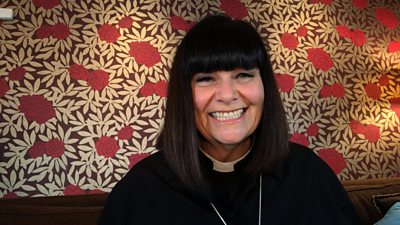 Dawn French as the Vicar of Dibley smiling in front of some flowery wallpaper