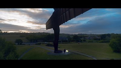 A man watches television at the feet of the Angel of the North