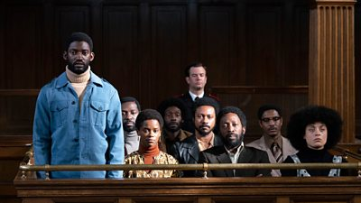 A black man stands up in court