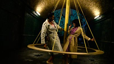 A couple dance around a swing in an underground vault