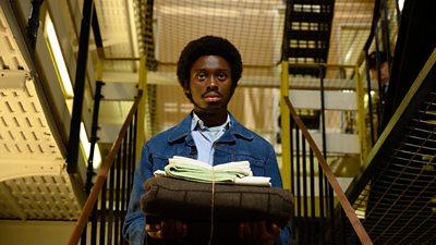 A young black man carries a bundle of linen inside a prison