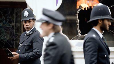 A black policeman stares at a colleague