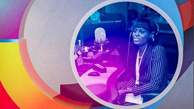 Woman in radio studio with headpphones in front of microphone