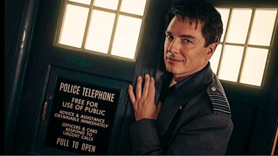 John Barrowman MBE as Captain Jack Harkness steps through the door of the TARDIS