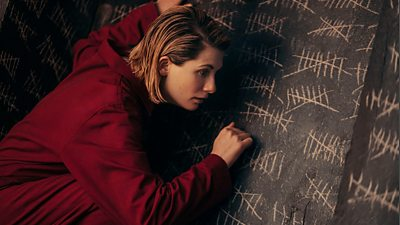 The Doctor (Jodie Whittaker) taps against a wall covered in tally marks