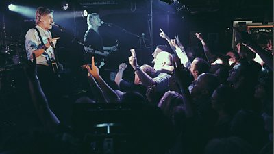 Paul McCartney on stage at a secret gig at The Cavern Club in Liverpool in July 2018, fans face him with their arms in the air