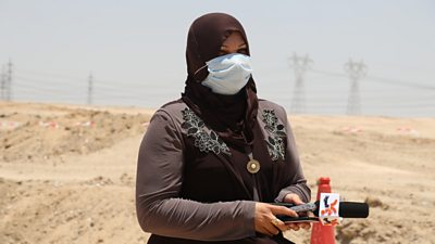 Al Mirbad editor Nihad al Jaberi shown with a microphone in a dusty outdoor setting