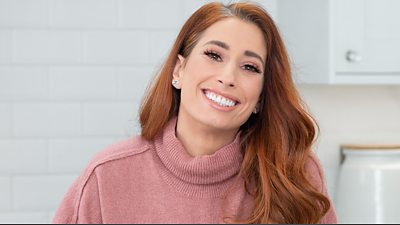 Stacey Solomon smiling wearing a pink jumper and sitting in a white kitchen
