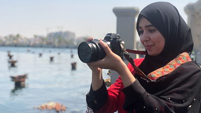 An El Kul journalist holds a camera preparing to take a photo.