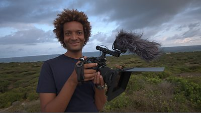 Jahawi is standing on moorland overlooking the sea, he's holding a camera with a microphone and wind muffler attached
