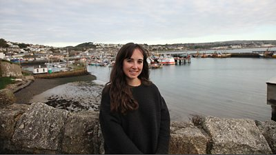 Megan has long brown hair and wears a dark jumper, she is standing in front of a small fishing harbour
